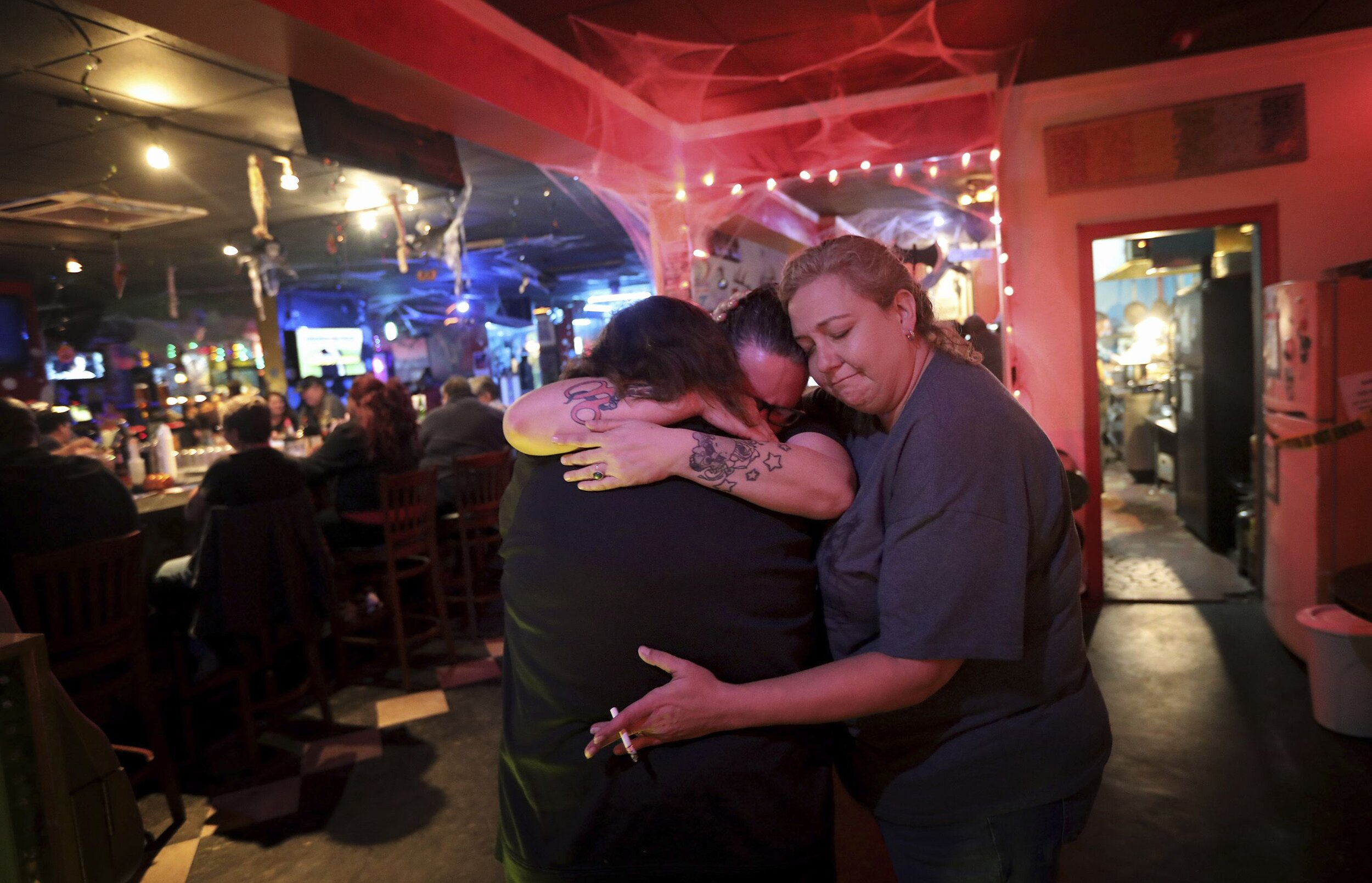 Three woman hug in the last days of Hershee Bar, one of the oldest lesbian bars on the East Coast. It closed in 2018 after 35+ years of operation in Norfolk.